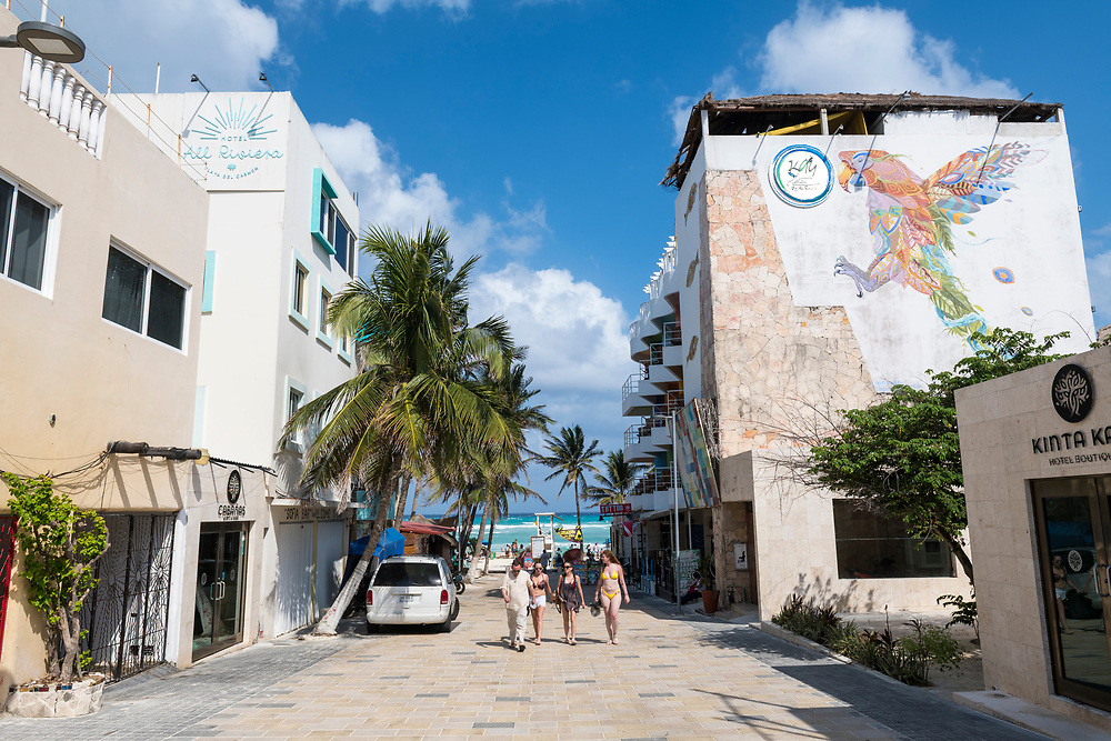 Playa del Carmen, Mexico - May 4, 2021: Visitors to Playa del Carmen walk away from the beach toward the town center on a sunny afternoon.