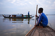 FISHERMEN MEKONG RIVER. South East Asia, Cambodia, Phnom Penh, Mekong River. The Cham fisher people live in various desolated villages along the banks of the Mekong and Tonle Sap rivers. The fisher families live like river gypsy nomads, working and living on their boats, sleeping under a sprung bamboo frame, all their worldly goods stored below deck. They live in extended families, with numerous boats, together for safety. Their diet is rice, vegetables and fish. Their sleek wooden boats are powered by petrol outboard motors with batteries or generators to supply lighting at night. Their fishing technique is laying nets twice or three times per day, which are weighted well below the surface, using old paint aerosal canisters as buoyant floaters, hanging just beneath the surface. These particular fisher families, living at the junction of the Mekong and Tonle Sap rivers, overlooked by Phnom Penh, sell their catch at the Vietnamese market, on the banks of the river. Their life and fortunes are controlled by the cycle of the river. As the river levels drop, so the quantity of fish decreases, until after the heavy floods of the monsoon they fill the river again. They are poor traditional Muslims, marginalised from mainstream society, living a third world life in the immmediate shadow of the first world. The Cham, originally a people of an ancient kingdom called Champa, are a small and disenfranchised community who were disinherited of their land. They are a socially important ethnic group in Cambodia, numbering close to 300,000. The Cham people, live in some 400 villages across Kampong Chnang and Kampong Cham provinces. Their religion is Muslim and their language belongs to the Malayo-Polynesian family. Their livelihoods are as diverse as rice farming, cattle trading, hunting and fishing.///Cham fishermen on the waters of the Mekong river