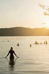 Mature woman walking in lake during sunset and her friends swimming in lake, Bavaria, Germany