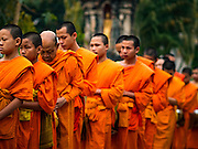 "11 MARCH 2016 - LUANG PRABANG, LAOS:   Buddhist monks walk down a street in Luang Prabang during the morning tak bat. Luang Prabang was named a UNESCO World Heritage Site in 1995. The move saved the city's colonial architecture but the explosion of mass tourism has taken a toll on the city's soul. According to one recent study, a small plot of land that sold for $8,000 three years ago now goes for $120,000. Many longtime residents are selling their homes and moving to small developments around the city. The old homes are then converted to guesthouses, restaurants and spas. The city is famous for the morning ""tak bat,"" or monks' morning alms rounds. Every morning hundreds of Buddhist monks come out before dawn and walk in a silent procession through the city accepting alms from residents. Now, most of the people presenting alms to the monks are tourists, since so many Lao people have moved outside of the city center. About 50,000 people are thought to live in the Luang Prabang area, the city received more than 530,000 tourists in 2014.     PHOTO BY JACK KURTZ"