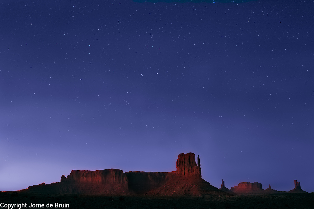 Monument Valley under a nightsky with stars.