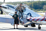 Montgomery, New York - A Collings Foundation crew member stands on the wing to open the cockpit of a P-51 Mustang fighter plane on the runway at Orange County Airport on Oct. 2, 2010.