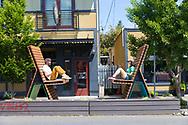 Two people enjoy oversized chairs in the NE Alberta Arts Neighborhood, Portland, OR, USA