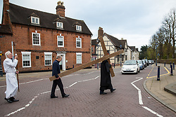 © Licensed to London News Pictures. 14/4/2016. Solihull, West Midlands, UK.  Easter Walk of Witness taking place in Solihull. Pictured, the procession makes it's way to St Alphege Church, stopping traffic on the main road in Solihull. All the churches of Solihull coming together. Starting at St Augustine's Church around two hundred people walked behind a wooden cross into Mell Square for readings and prayers before continuing the walk to St Alphege Church.  Photo credit: Dave Warren/LNP