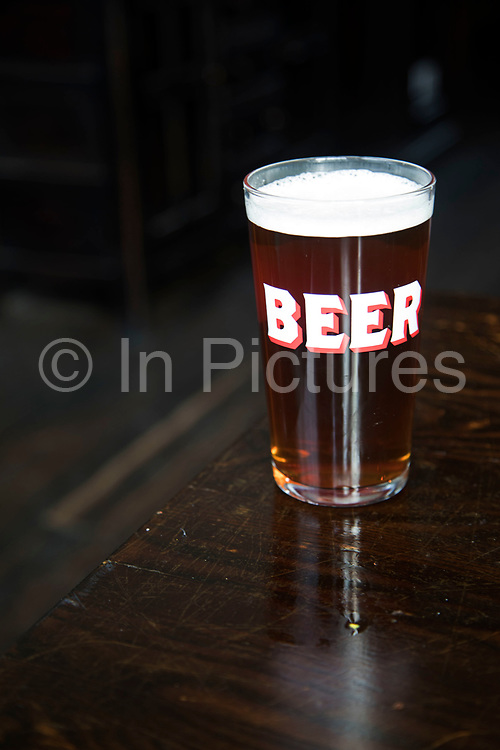 A pint glass of real ale on a pub table in Birmingham, United Kingdom. Sales of these ales is on the increase, where other alcolholic beer and beverages are on the decline.