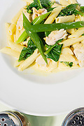 A serving of Penne pasta with cream sauce and greens