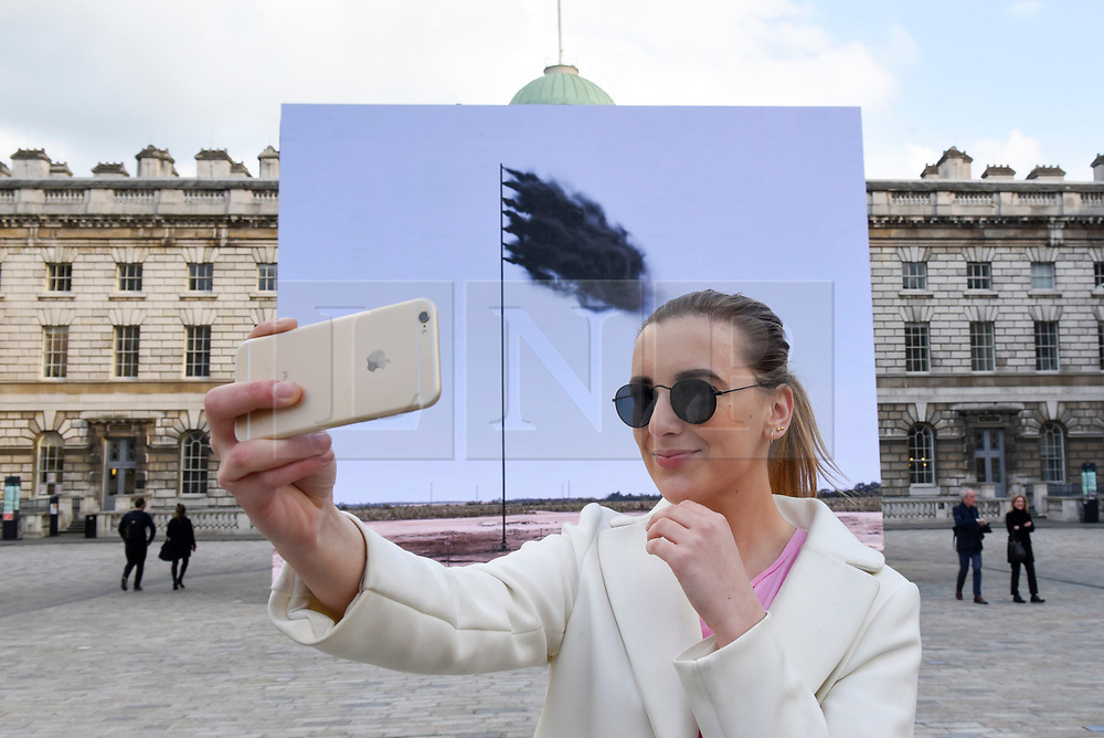 "© Licensed to London News Pictures. 20/04/2017. London, UK. A woman takes a selfie at the unveiling at Somerset House of ""Western Flag"" (Spindletop, Texas) 2017 by artist John Gerrard.  The artwork, in the form of an LED wall installation, is a symbol for climate change and modern society's dependence on oil and has been commissioned by Channel 4 as part of their Man-Made Planet season to mark this year's Earth Day (22nd April).   Photo credit : Stephen Chung/LNP"