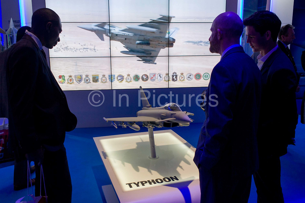Visitors admire the features of the BAE Systems Typhoon jet fighter presentation model, exhibited at the Farnborough Air Show, England. The Typhoon was designed and is manufactured by a consortium of three companies; BAE Systems, Airbus Group and Alenia Aermacchi, who conduct the majority of affairs dealing with the project through a joint holding company, Eurofighter Jagdflugzeug GmbH, which was formed in 1986. The project is managed by the NATO Eurofighter and Tornado Management Agency, which also acts as the prime customer. BAE Systems plc is a British multinational defence, security and aerospace company headquartered in London in the United Kingdom and with operations worldwide.