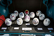 Painted ostrich eggs in the boot of a Vauxhall car by artist Kate Knight on sale at the 2017 Art Car Boot Fair, Folkestone, Kent.