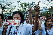 """12 JANUARY 2014 - BANGKOK, THAILAND: Women carry stickers supporting the February 2 election in Thailand. About 500 people from all walks of Thai life came to a candlelight vigil at Thammasat University. They prayed for a peaceful resolution to the political conflict in Thailand. They finished the vigil by singing the John Lennon song """"Imagine."""" Anti-government protestors are expected """"Shutdown Bangkok"""" Monday. There were reports Sunday evening that some intersections were already being blocked.       PHOTO BY JACK KURTZ"""
