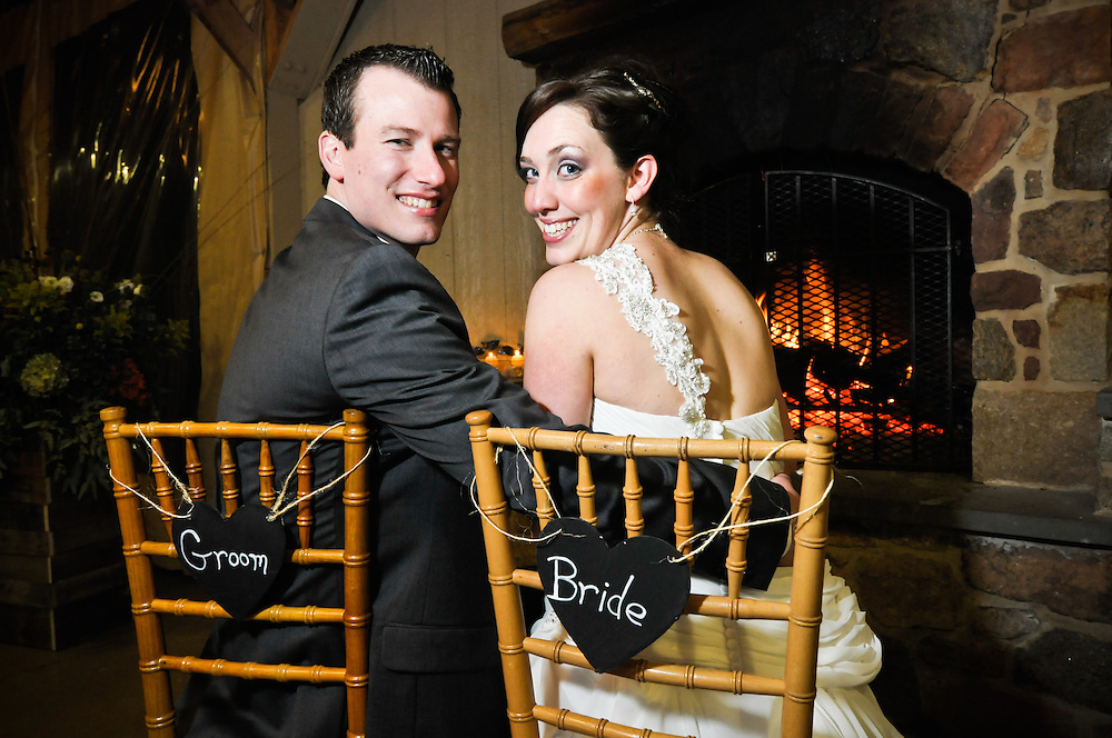 A bride and groom enjoy a moment by the fire at the Audubon Center at Mill Grove, <br /> PA.