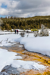 A couple of winter visitors departing Biscuit Basin to board the snowcoach beyond to see more wonders of Yellowstone.