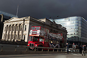 Under a heavy sky, a Classic Tour tour bus drives south to pass Fishmongers Hall and crosses London Bridge in the City of London, the capitals financial district, on 28th January 2020, in the City of London.