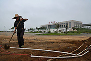 A man works on a road construction project in front of the Dingyuan rail station, the only rural county level station along the Beijing-Shanghai High-Speed Railway, in Dingyuan County, Anhui Province, China on 16 August 2012.  Dingyuan is the ancestral home of Chinese vice premier Li Keqiang, who is widely accepted as the next premier, the third most powerful position in the Chinese political hierarchy, after Wen Jiabao steps down in late 2012.
