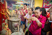"""10 FEBRUARY 2013 - BANGKOK, THAILAND:  People pray at a Chinese temple in Bangkok on Chinese New Year. Bangkok has a large Chinese emigrant population, most of whom settled in Thailand in the 18th and 19th centuries. Chinese, or Lunar, New Year is celebrated with fireworks and parades in Chinese communities throughout Thailand. The coming year will be the """"Year of the Snake"""" in the Chinese zodiac.   PHOTO BY JACK KURTZ"""