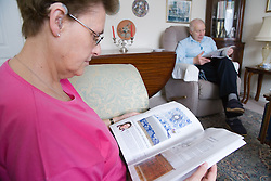 Older couple relaxing at home reading,