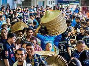 18 SEPTEMBER 2017 - BANGKOK, THAILAND: A volunteer carries a stack of baskets through the crowd at Poh Teck Tung. The baskets are given to people to help them carry the food they get. The Ghost Festival, also known as the Hungry Ghost Festival, Zhongyuan Festival or Yulan Festival is a traditional Buddhist and Taoist festival held in Asian countries. According to the Chinese calendar (a lunisolar calendar), the Ghost Festival is on the 15th night of the seventh month. In Chinese culture, the fifteenth day of the seventh month in the lunar calendar is called Ghost Day and the seventh month in general is regarded as the Ghost Month, in which ghosts and spirits, including those of the deceased ancestors, come out from the lower realm. Distinct from both the Qingming Festival (in spring) and Double Ninth Festival (in autumn) in which living descendants pay homage to their deceased ancestors, during Ghost Festival, the deceased are believed to visit the living.     PHOTO BY JACK KURTZ