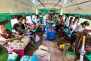 15 JUNE 2013 - YANGON, MYANMAR: A passenger compartment on the Yangon Circular Railway. The Yangon Circular Railway is the local commuter rail network that serves the Yangon metropolitan area. Operated by Myanmar Railways, the 45.9-kilometre (28.5mi) 39-station loop system connects satellite towns and suburban areas to the city. The railway has about 200 coaches, runs 20 times and sells 100,000 to 150,000 tickets daily. The loop, which takes about three hours to complete, is a popular for tourists to see a cross section of life in Yangon. The trains from 3:45 am to 10:15 pm daily. The cost of a ticket for a distance of 15 miles is ten kyats (~nine US cents), and that for over 15 miles is twenty kyats (~18 US cents). Foreigners pay 1 USD (Kyat not accepted), regardless of the length of the journey.     PHOTO BY JACK KURTZ