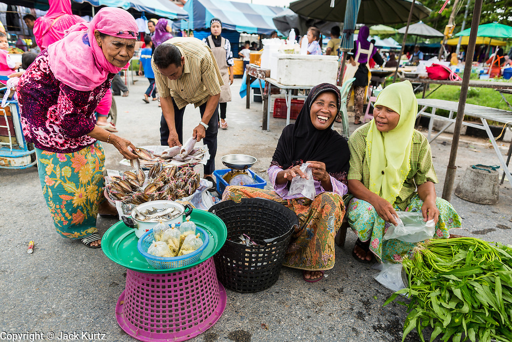 10 JULY 2013 - PATTANI, PATTANI, THAILAND:  A Muslim woman looks at fish to buy for Iftar at a night market in Pattani, Thailand. Iftar is the meal Muslims take when they break their daily Ramadan fast. Ramadan is the ninth month of the Islamic calendar, and the month in which Muslims believe the Quran was revealed. Muslims believe that the Quran was sent down during this month, thus being prepared for gradual revelation by Jibraeel (Gabriel) to the prophet Muhammad.  The month is spent fasting during the daylight hours from dawn to sunset. Fasting during the month of Ramadan is one of the Five Pillars of Islam.     PHOTO BY JACK KURTZ