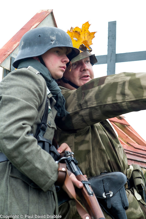 Re-enactors portraying German Infantry from the 276 Volksgrenadier Division take part in a battle at the Pickering Wartime weekend showground. Both are wearing the iconic German Steel Helmet (Stahlhelm) and one is carrying the Standard German infantry rifle a Mauser K98-kar<br /> <br /> 17/18 October 2015<br />  Image © Paul David Drabble <br />  www.pauldaviddrabble.co.uk