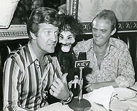 "1976 Radio commentator and interviewer, Gregg Hunter, seen interviewing puppeteer, Wayland Flowers and puppet, ""Madame"" during his KIEV radio show at the Brown Derby Restaurant on Vine St. in Hollywood"