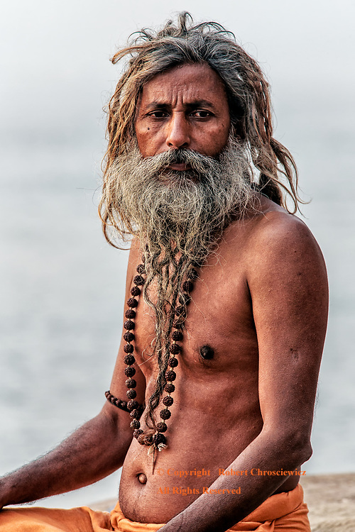 Reflective Sadhu: A bare chested Hindu Sadhu sits by the Ganges River sporting a wildly extravagant hair style; with braided hair and beard that compliment the characteristic Dharma prayer beads, Varanasi India.