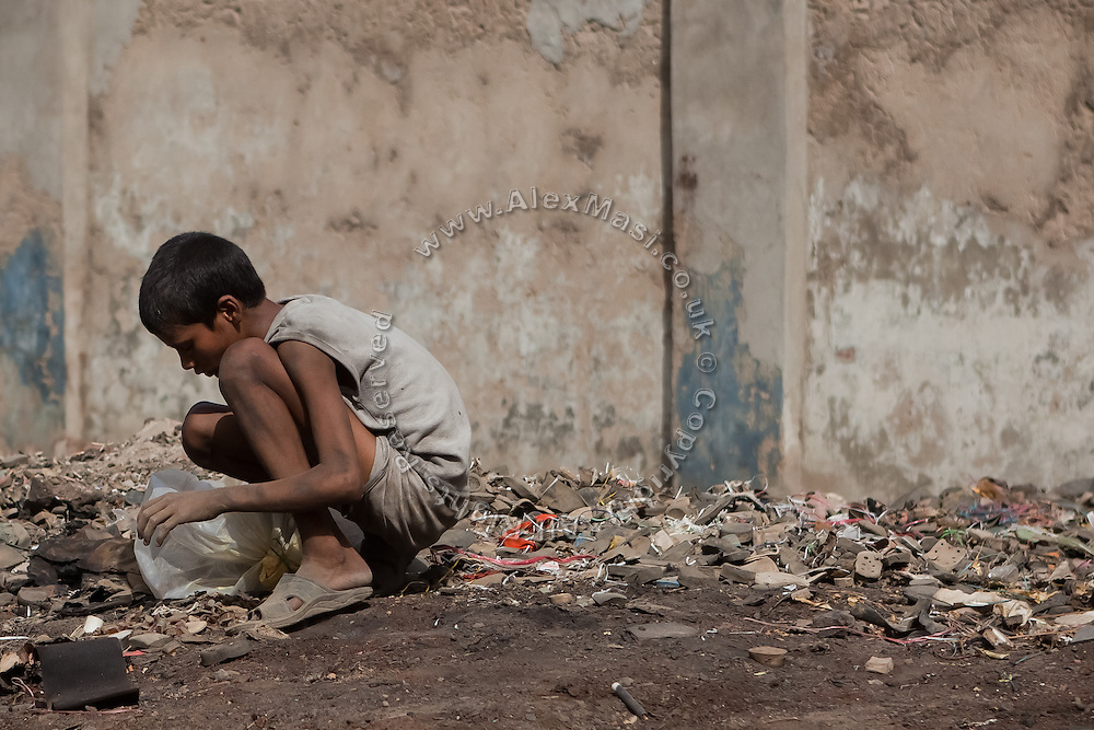 A child is collecting useful items from scraps at the industrial area of Agra.