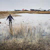 Nederland, Amsterdam, 24 maart 2016.<br /> tijdelijke natuur. Stadsecoloog Martin Melchers is belast met de opdracht om een natuurgebied te verhuizen. Volgend jaar komt er een bedrijf op het terrein. <br /> Op de foto: Stadsecoloog Martin Melchers wadend door de plassen in het natuurgebied rond het Westelijk Havengebied langs het Noordzeekanaal.<br /> <br /> <br /> Temporary nature. City ecologist Martin Melchers is commissioned to move a nature reserve. Next year there will be a business on the premises.<br /> In the photo : City ecologist Martin Melchers wading through the puddles in the area around the western harbor area along the North Sea Canal. <br /> <br /> Foto: Jean-Pierre Jans
