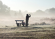 © Licensed to London News Pictures. 06/11/2014. Richmond, UK. A man takes a picture of the wintery scene.  People and animals during a frosty start to the day on 6th November 2014. Temperature fell across the country overnight. Photo credit : Stephen Simpson/LNP