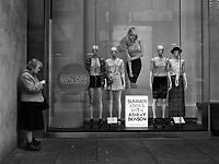 Woman tuning in for a summer look in front of H&M  on Fifth Avenue and 43rd street, New York City