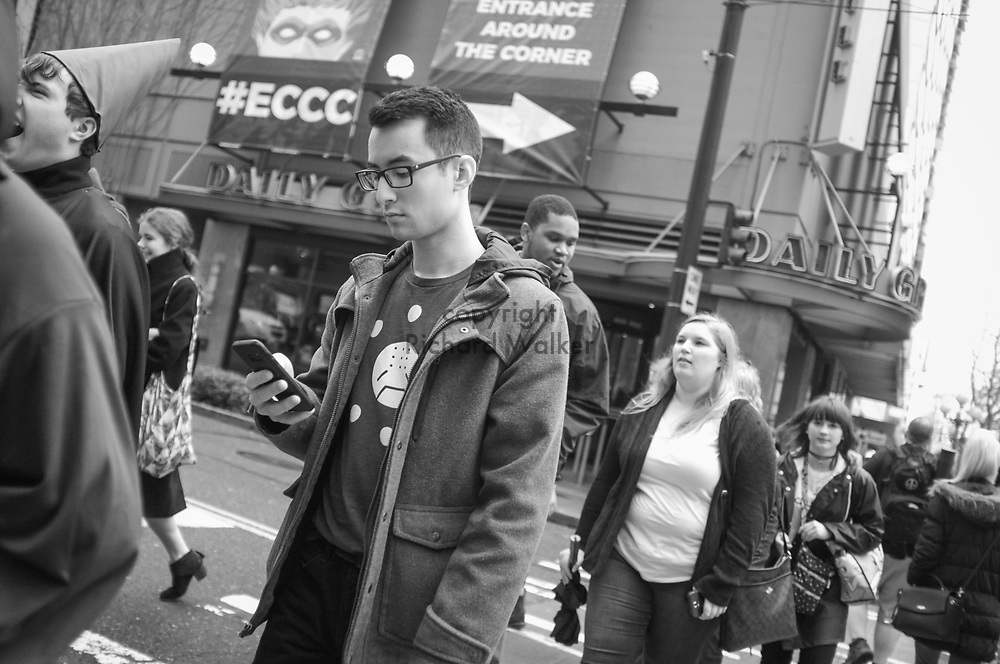 2017 MARCH 05 - A man looks at his cell phone at the corner of 7th and Pine Street near Emerald City Comicon, downtown, Seattle, WA, USA. By Richard Walker