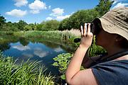 Woman birdwatching, Barnes, London, UK, looking through binoculars at birds on water