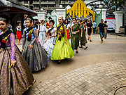 """08 APRIL 2017 - BANGKOK, THAILAND: Entertainers walk into the """"Amazing Songkran"""" festival in Benchasiri Park in Bangkok. The festival was sponsored by the Tourism Authority of Thailand to highlight the cultural aspects of Songkran. Songkran is celebrated in Thailand as the traditional New Year's Day from 13 to 16 April. Songkran is in the hottest time of the year in Thailand, at the end of the dry season and provides an excuse for people to cool off in friendly water fights that take place throughout the country. Songkran has been a national holiday since 1940, when Thailand moved the first day of the year to January 1. Songkran 2017 is expected to be more subdued than Songkran usually is because Thais are still mourning the October 2016 death of revered King Bhumibol Adulyadej.       PHOTO BY JACK KURTZ"""