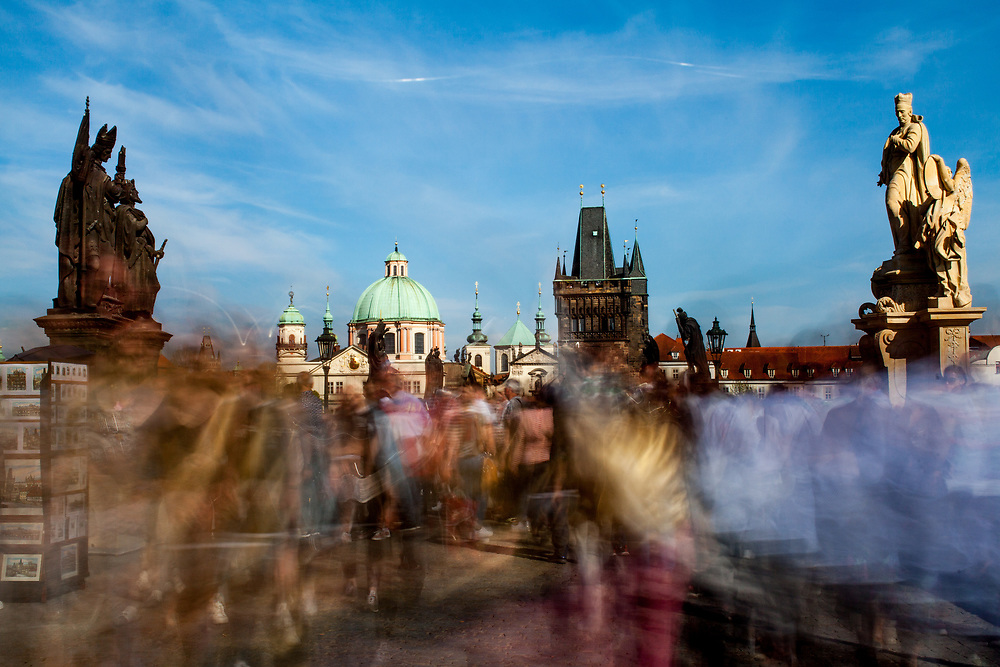 Crowds visiting the Charles Bridge which is a historic bridge that crosses the Vltava river in Prague and one of the main attractions in the city. Its construction started in 1357 under the auspices of King Charles IV and finished in the beginning of the 15th century.