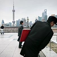 China, Shanghai,maart 2008..Wandelaars op de Bund, de koloniale boulevard langs de Huangpu-rivier. De boulevard is in 1992 veranderd in een brede wandelpromenade..Vanaf de Bund ziet u aan de overkant van de Huangpu het nieuwe Pudong verrijzen. Deze wijk moet het hart van de handel en financiën van Shanghai gaan worden. Aan de nieuwbouw wordt dan ook veel zorg besteed en u vindt er veel fraaie voorbeelden van moderne architectuur. Een kenmerkend gebouw in Pudong is de Televisietoren. U kunt er met een snelle lift naar boven en u hebt dan een weids uitzicht over oud en nieuw Shanghai.