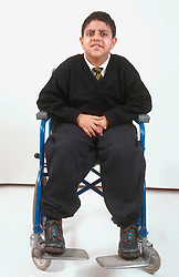Studio portrait of teenage boy with disability; who is wheelchair user,