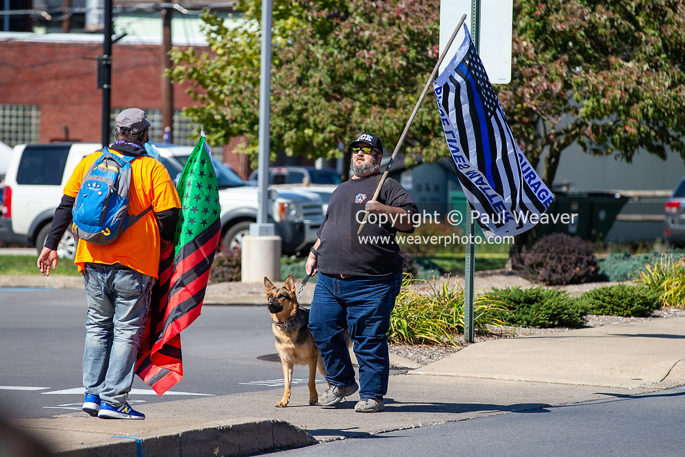 A counter-protester carrying a blue lives matter flag approaches a a Black Lives Matter rally.