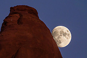 Moonrise at sunset seen from Devils Garden Campground, Arches National Park, Moab, Utah, USA.