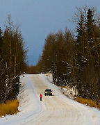 Alaska, Anchorage, Old Seward Highway, Person running on Old Seward Highway with a vehicle passing