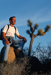 Male hiker seated on a rock in Joshua Tree National Park, CA