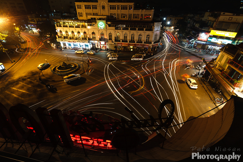 Overhead view of busy Hanoi intersection at night with light trails