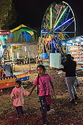 Young children walk through a tiny traveling carnival during celebrations marking the Day of the Dead festival n the tiny Purepecha town of Ihuatzio, Michoacan, Mexico.