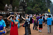 Chinese tourists on the South Bridge crossing the moat to Ankor Thom
