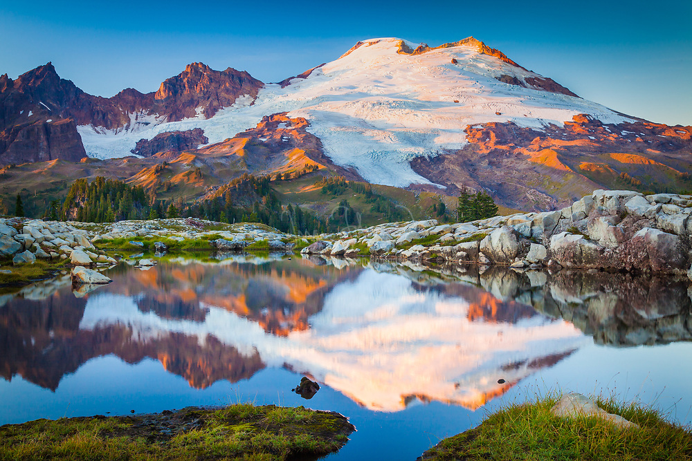 "Mount Baker reflecting in tarn near Park Butte in the Mount Baker Wilderness <br /> ..... <br /> Mount Baker, also known as Koma Kulshan or simply Kulshan, is an active glaciated andesitic stratovolcano in the Cascade Volcanic Arc and the North Cascades of Washington State in the United States. Mount Baker has the second-most thermally active crater in the Cascade Range after Mount Saint Helens. About 31 miles due east of the city of Bellingham, Whatcom County, Mount Baker is the youngest volcano in the Mount Baker volcanic field. While volcanism has persisted here for some 1.5 million years, the current glaciated cone is likely no more than 140,000 years old, and possibly no older than 80-90,000 years. <br /> After Mount Rainier, Mount Baker is the most heavily glaciated of the Cascade Range volcanoes; the volume of snow and ice on Mount Baker, 0.43 cu mi is greater than that of all the other Cascades volcanoes (except Rainier) combined. At 10,781 ft, it is the third-highest mountain in Washington State and the fifth-highest in the Cascade Range, if Little Tahoma Peak, a subpeak of Mount Rainier, and Shastina, a subpeak of Mount Shasta, are not counted. Located in the Mount Baker Wilderness, it is visible from much of Greater Victoria, Greater Vancouver, and, to the south, from Seattle (and on clear days Tacoma) in Washington. <br /> Indigenous natives have known the mountain for thousands of years, but the first written record of the mountain is from the Spanish. Spanish explorer Gonzalo Lopez de Haro mapped it in 1790 as the Gran Montana del Carmelo, ""Great Mount Carmel"". The explorer George Vancouver renamed the mountain for 3rd Lieutenant Joseph Baker of HMS Discovery, who saw it on April 30, 1792."