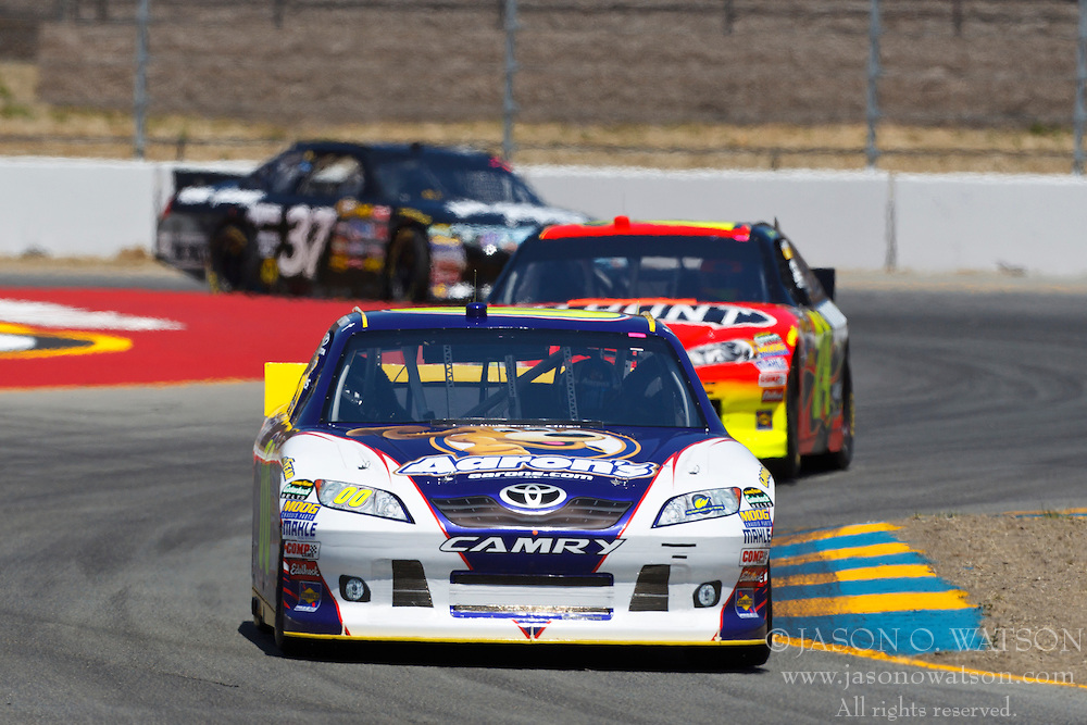 June 24, 2011; Sonoma, CA, USA;  NASCAR Sprint Cup Series driver David Reutimann (00) leads driver Jeff Gordon (24) and driver Chris Cook (37) through turn 7 during practice for the Toyota/Save Mart 350 at Infineon Raceway.
