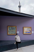 A member of the public stretches in front of copies of selected paintings, a temporary display of historical art placed outside the National Gallery to show passers-by what can be seen in their galleries, on 1st September 2021, in Trafalgar Square, London, England.