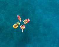 Aerial view of women in bikinis holding hands on inflatable mattresses on Atokos island, Greece.