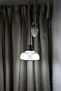 hanging from ceiling glass lamp shade with light on against closed curtains