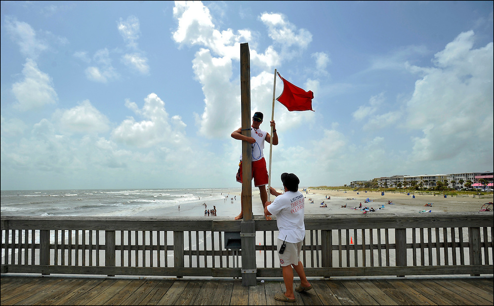 """Tybee Island Ocean Rescue lifeguards Andrew Robinson, center, and Jonathan """"J.T."""" Thomas, right, raise a high hazard warning flag for dangerous rib currents on the pier in Tybee Island, Ga., Thursday, Aug. 25, 2011. Tybee, one of Georgia's few out island communities, is only expecting high surf from Hurricane Irene as the storm passes to the west on Friday. (AP Photo/Stephen Morton)"""