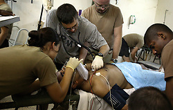 Members of Company C, 407th Forward Support Battalion, 82nd Airborne Division known as the Charlie Med, treat Ed Emad Eada, Baghdad, Iraq, Aug. 10, 2003. Eada, an Iraqi translator for the 82nd Airborne, was shot for aiding Americans outside his home in Baghdad.